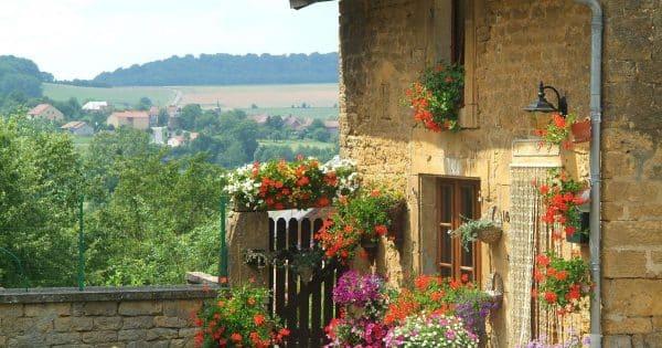 Façade fleurie avec arrière plan de vallée gaumaise ensoleillée